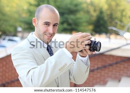Attractive, Young Mature Professional Photographer Business Man Smiling While Taking a Picture - stock photo