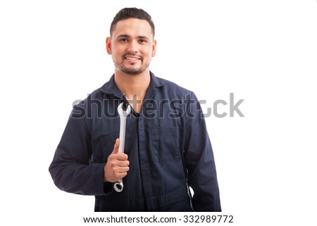 Attractive young mechanic wearing overalls and holding a wrench on a white background - stock photo