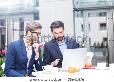 Attractive young men have a business lunch - stock photo