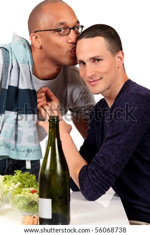 Attractive young mixed ethnicity gay, homosexual couple, Caucasian and African American in kitchen, preparing salad for dinner.  Studio, white background.