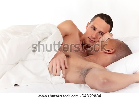 Attractive young mixed ethnicity gay, homosexual couple, Caucasian and African American men in the bedroom, grooming.  Studio, white background. - stock photo