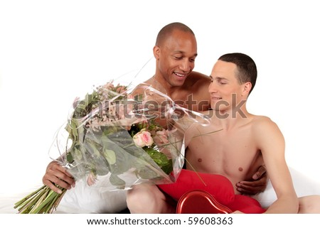 Attractive young mixed ethnicity gay, homosexual couple, Caucasian and African American men in the bedroom, grooming, celebrating valentines day with  bouquet of flowers.  Studio, white background. - stock photo
