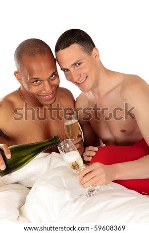 Attractive young mixed ethnicity gay, homosexual couple, Caucasian and African American men in the bedroom, grooming, drinking champagne.  Studio, white background. - stock photo