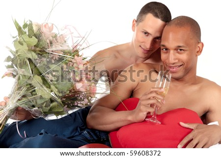 Attractive young mixed ethnicity gay, homosexual couple, Caucasian and African American men in the bedroom, celebrating valentines day with champagne and bouquet of flowers. - stock photo