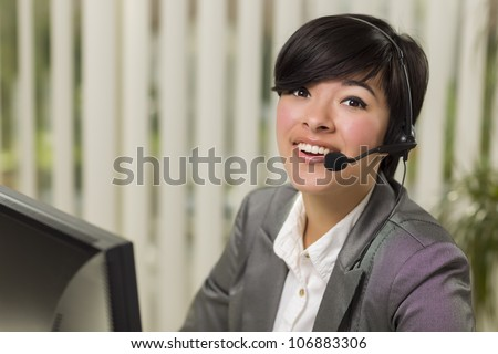Attractive Young Mixed Race Woman Smiles Wearing Headset Near Computer Monitor. - stock photo