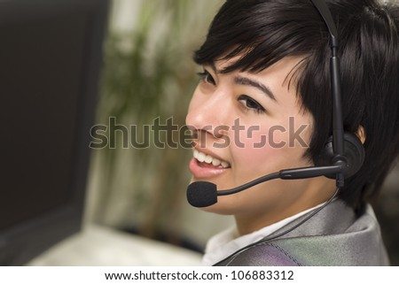 Attractive Young Mixed Race Woman Smiles Wearing Headset Near Computer Monitor.