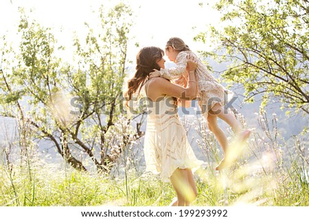 Attractive young mother and her beautiful daughter playing together in a spring garden with flowers and sunshine, carrying the child in her arms and joyfully turning around, smiling. Family lifestyle. - stock photo