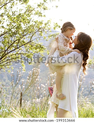 Attractive young mother and her beautiful daughter playing together in a spring garden with flowers and sunshine, carrying the child in her arms and joyfully smiling. Family outdoors lifestyle. - stock photo