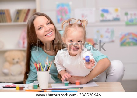 Attractive young mother and her daughter are painting pictures. They are sitting at the desk in the room at home. The woman is embracing the girl with love. They are smiling - stock photo