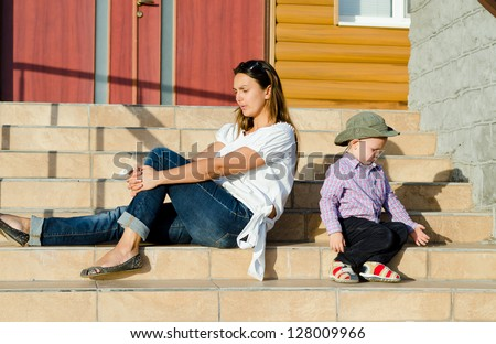 Attractive young mother and her small son sitting in the sun on the steps of a house ignoring one another facing in opposite directions - stock photo