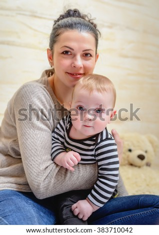 Attractive young mother hugging her little baby close to her chest with her cheek resting tenderly on its head as they both smile happily at the camera, close up face portrait - stock photo