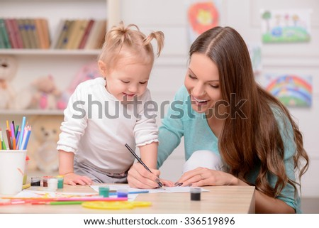 Attractive young mother is drawing with her daughter. The girl is standing and looking at the picture with amazement. The woman is sitting at the table and smiling - stock photo