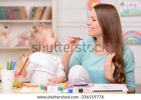 Attractive young mother is teaching her daughter painting. She is applying paint on nose of girl with fun. They are sitting at the table and laughing - stock photo