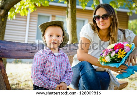 Attractive young mother sitting on a garden bench with her small son on Mothers Day holding a colourful bouquet of flowers that he has just given her as a gift - stock photo