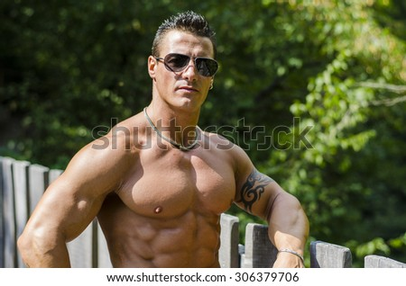 Attractive young muscleman outdoors, leaning on metal hand railing - stock photo