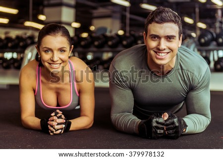 Attractive young muscular man and woman doing plank exercise and smiling while working out in gym - stock photo