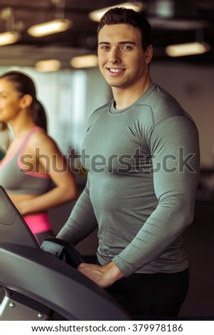 Attractive young muscular man running on a treadmill in gym, looking at camera and smiling - stock photo