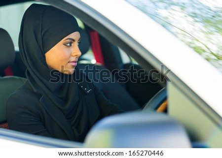 attractive young muslim woman driving a car - stock photo