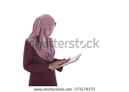 Attractive young muslimah businesswoman calculating her expenditure. - stock photo