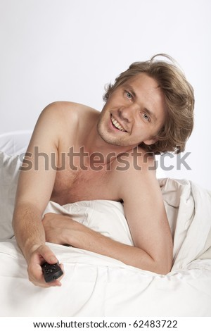 Attractive young naked man lying in bed and having fun watching tv. Studio shot. See more in my portfolio - stock photo