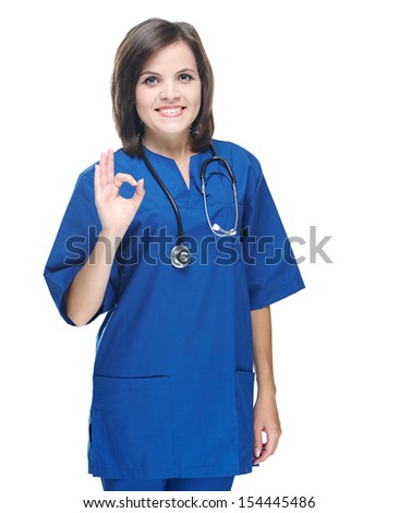 Attractive young nurse in uniform. Shows sign okay. Isolated on white background