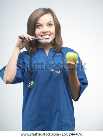 Attractive young nurse with a stethoscope. Holding a toothbrush and a green apple. On a gray background - stock photo