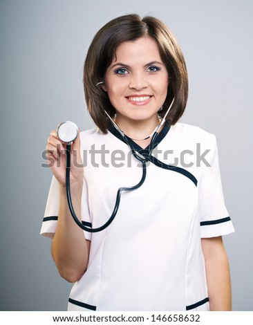 Attractive young nurse with a stethoscope.  Isolated on a gray background