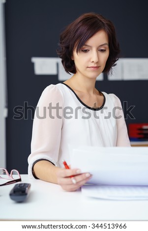 Attractive Young Office Woman Reading Some Business Documents at her Desk Seriously. - stock photo
