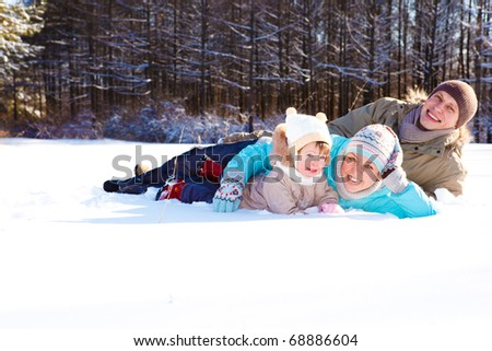 Attractive young parents and their daughter lying in snow - stock photo