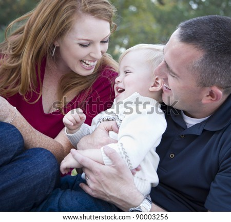 Attractive Young Parents Laughing with their Child Boy in the Park. - stock photo