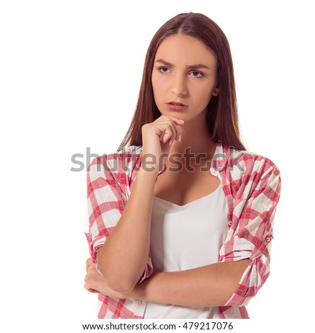 Attractive young pensive girl in casual clothes is keeping hand on chin, looking away and thinking, isolated on white background