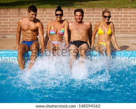 Attractive young people having summer fun by outdoor swimming pool, smiling. - stock photo