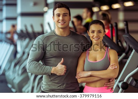 Attractive young people standing in gym and smiling. Man showing OK sign. - stock photo