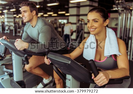 Attractive young people working out on an exercise bike in gym and smiling