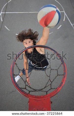 attractive young person with basketball ball - focused on the basket - stock photo