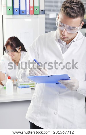 Attractive young PhD student scientist with colleague out of focus behind him in chemical laboratory - stock photo