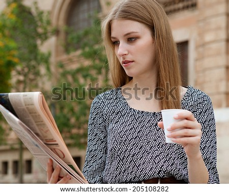 Attractive young professional business woman reading a financial newspaper while drinking coffee and using a laptop computer in a classic city. Business technology and communications, outdoors. - stock photo