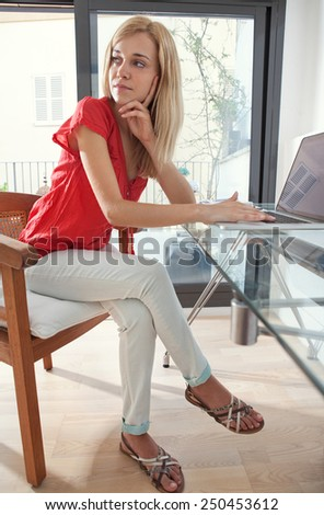 Attractive young professional woman being thoughtful in home office space, thinking and turning away. Student girl using a laptop computer at her home work desk. Lifestyle and technology, interior. - stock photo