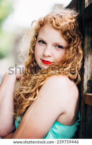 attractive young red head leaning against fence looking at camera slight smile, hugging herself, variation