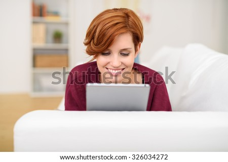 Attractive young redhead woman relaxing on a sofa in the living room using a tablet to browse the internet or read an e-book, smiling with pleasure, close up of her face - stock photo