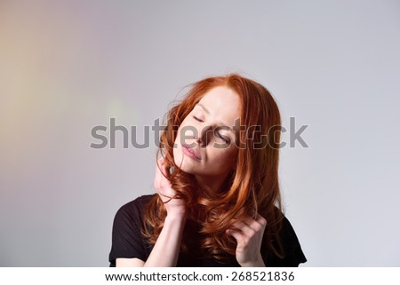 Attractive young redhead woman with a stiff neck standing rubbing it with her hand and eyes closed, over grey - stock photo