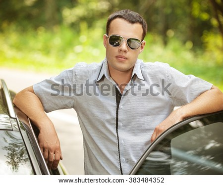 attractive young serious man standing next car sunglasses background summer green park - stock photo