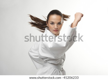 Attractive young sexy women in a karate pose isolated on white - stock photo