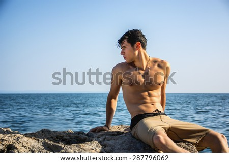Attractive young shirtless athletic man crouching in water by sea or ocean shore, wearing shorts, looking away to a side - stock photo