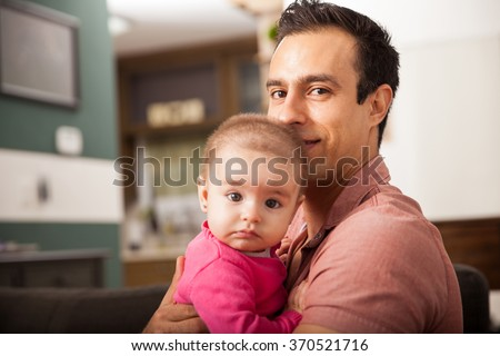 Attractive young single dad spending some time with his baby girl at home - stock photo
