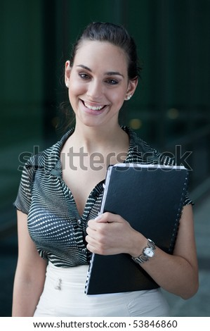 Attractive young smiling businesswoman standing in front of an office building