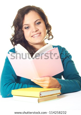 Attractive young smiling girl in a blue shirt sitting at a table and reading a pink book. Isolated on white background