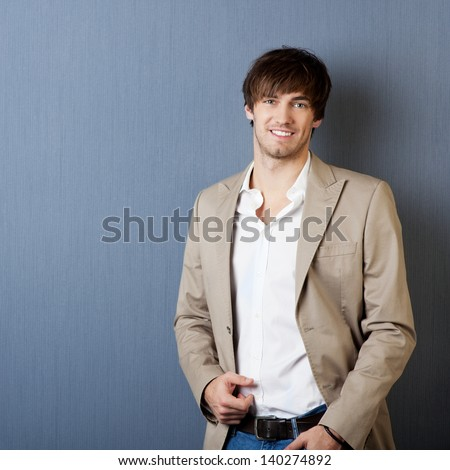 Attractive young smiling man with jacket on a blue background - stock photo