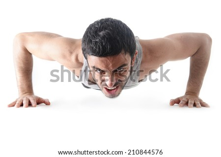attractive young sport man training his body doing push up exercise showing suffering and sacrifice face expression isolated on white background - stock photo