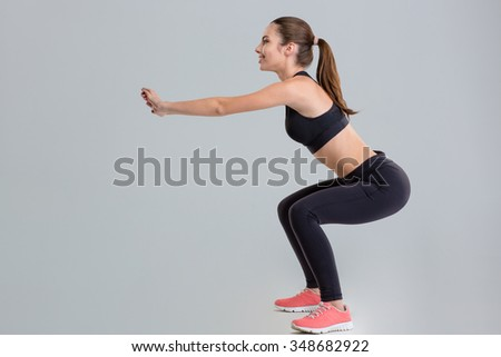 Attractive young sportswoman in sportwear doing squats isolated over grey background - stock photo